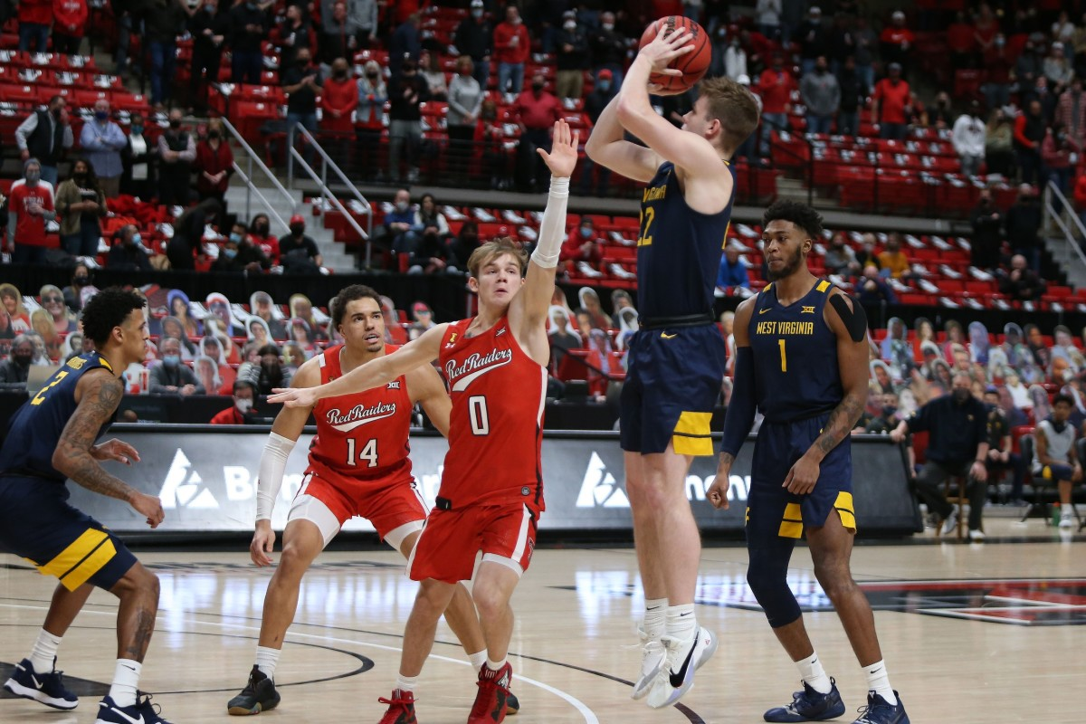 Feb 9, 2021; Lubbock, Texas, USA; West Virginia Mountaineers guard Sean McNeil (22) shoots over Texas Tech Red Raiders guard Mac McClung (0) in the first half at United Supermarkets Arena.