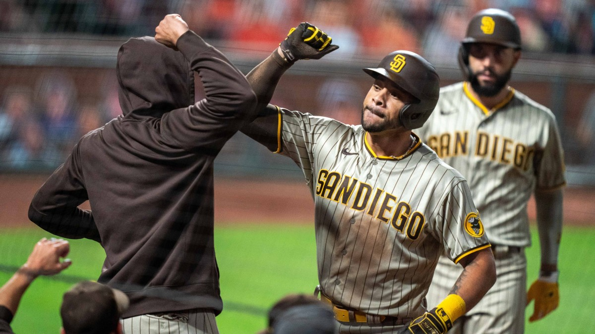 Padres' Tommy Pham elbows teammate after scoring a run.