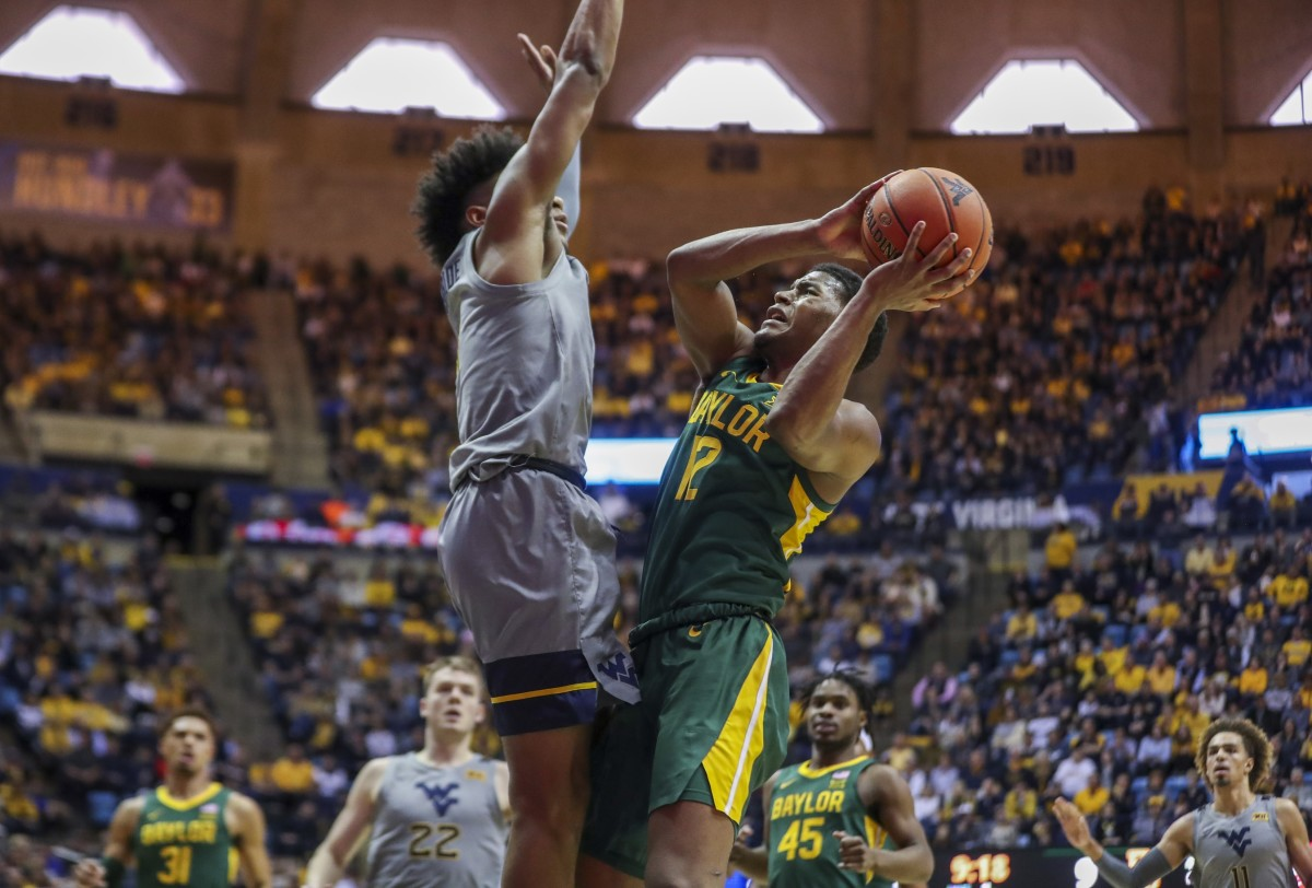 Mar 7, 2020; Morgantown, West Virginia, USA; Baylor Bears guard Jared Butler (12) shoots while defended by West Virginia Mountaineers guard Miles McBride (4) during the first half at WVU Coliseum.