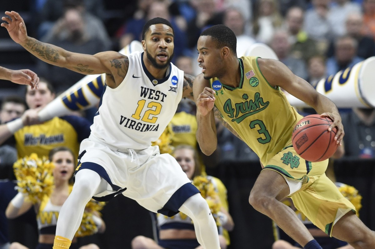 Mar 18, 2017; Buffalo, NY, USA; Notre Dame Fighting Irish forward V.J. Beachem (3) dribbles the ball against West Virginia Mountaineers guard Tarik Phillip (12) in the first half during the second round of the 2017 NCAA Tournament at KeyBank Center.