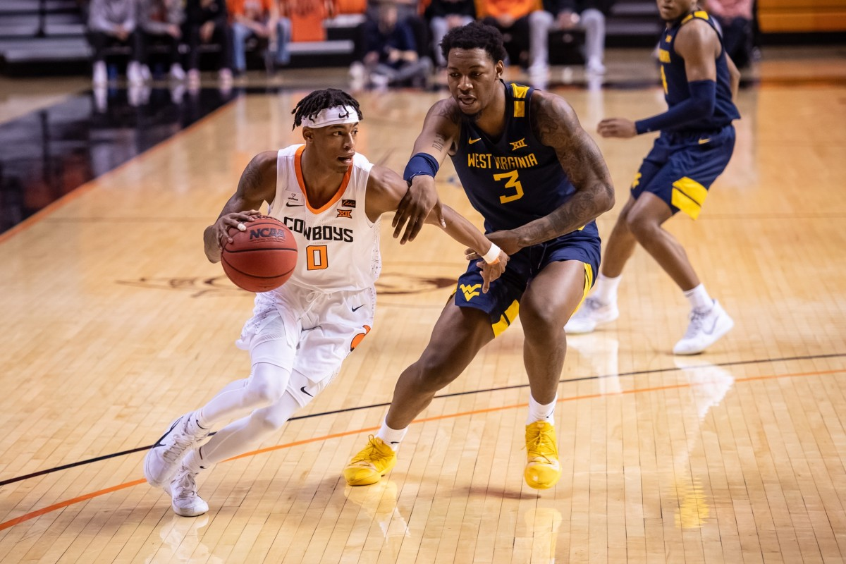 Jan 4, 2021; Stillwater, Oklahoma, USA; Oklahoma State Cowboys guard Avery Anderson III (0) dribbles past West Virginia Mountaineers forward Gabe Osabuohien (3) during the second half at Gallagher-Iba Arena.