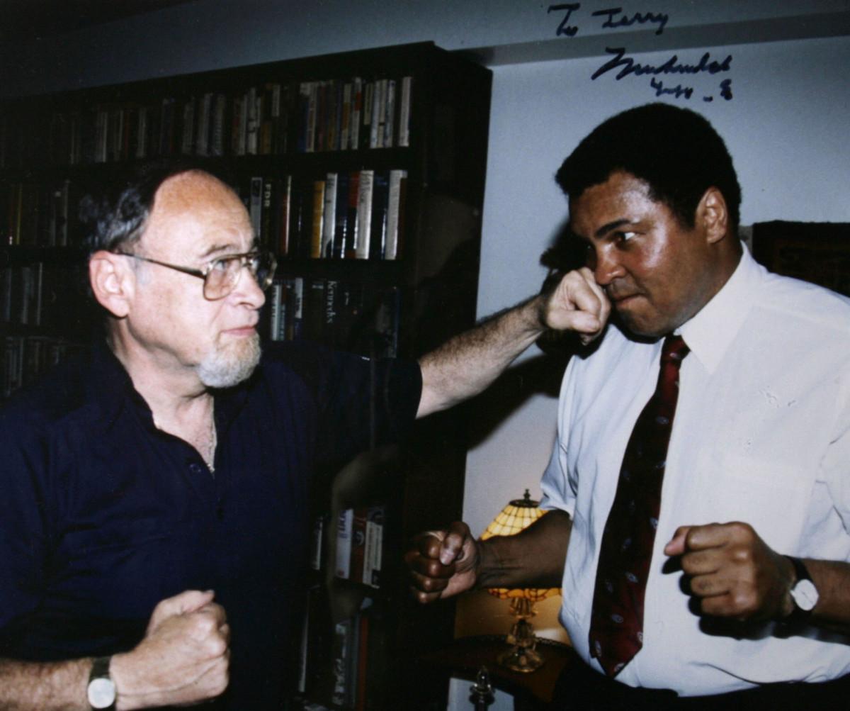 Sports writer Jerry Izenburg lands a friendly punch on Muhammad Ali.