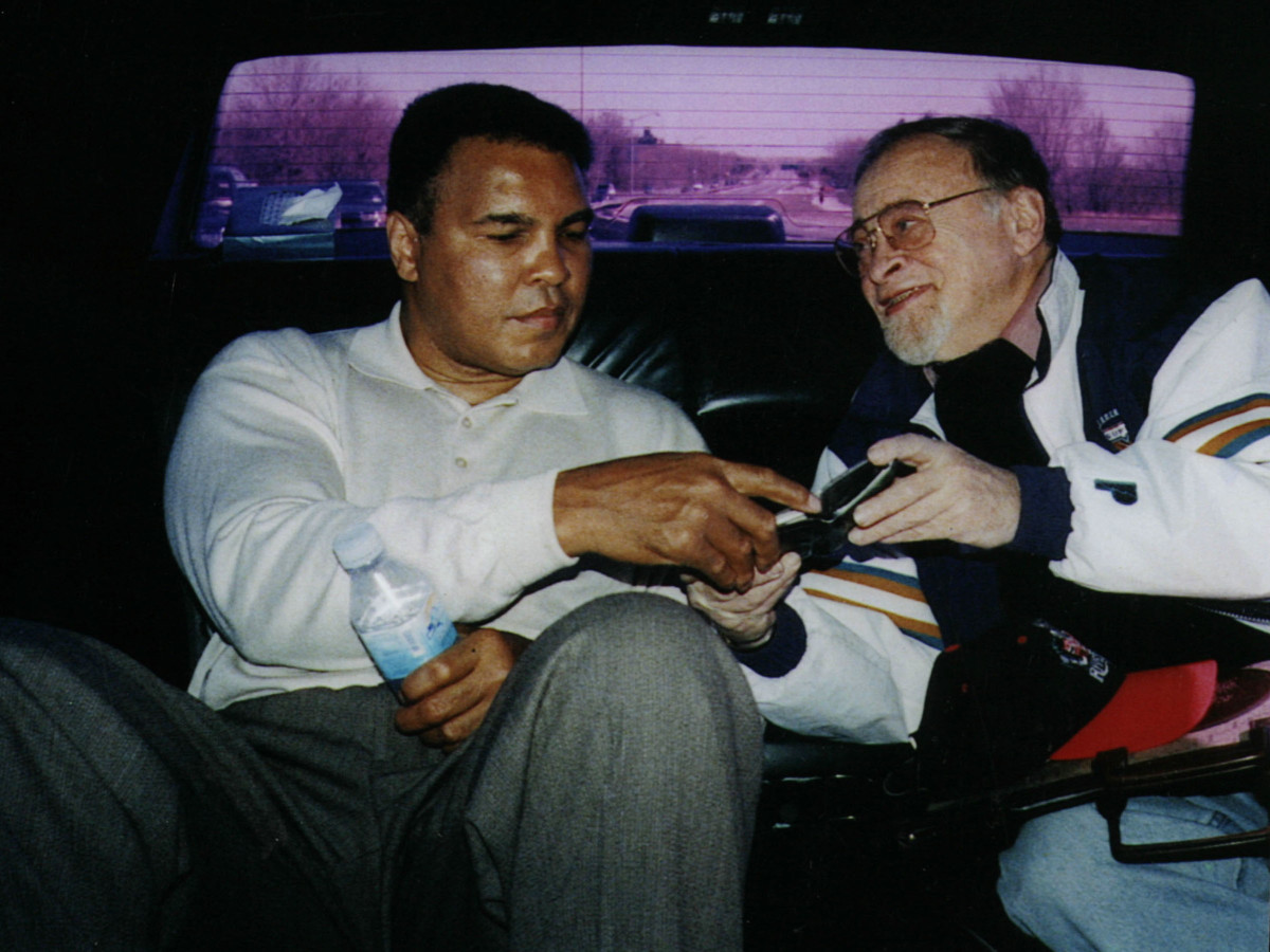 Muhammad Ali rides with Jerry Izenberg in the back of a car.