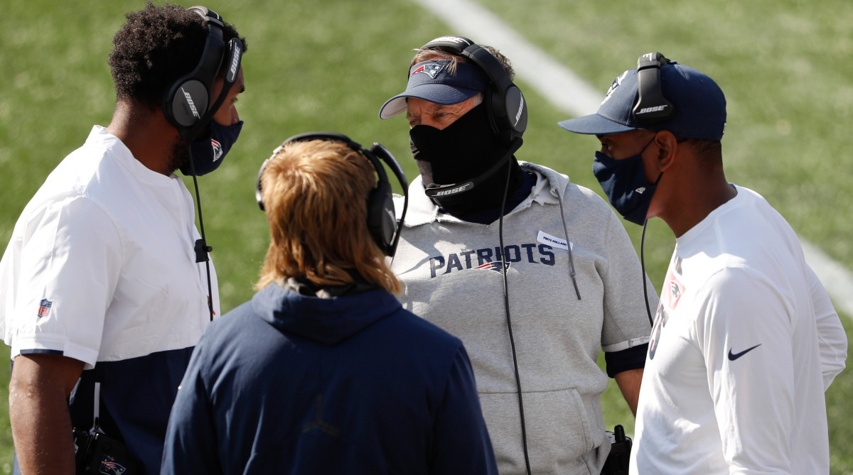 Patriots head coach Bill Belichick talks with other coaches