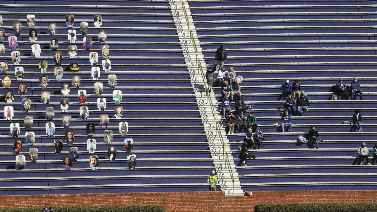 Fans at a Furman football game this spring sit one section away from cardboard cutouts.