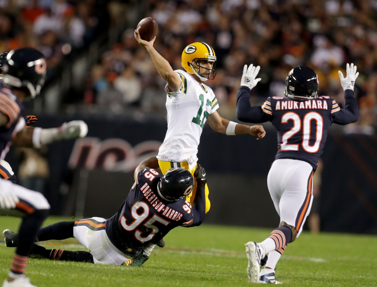 Green Bay quarterback Aaron Rodgers (12) attempts a pass while Bears defensive end Roy Robertson-Harris (95) attempts a tackle. Photo by Mike De Sisti/Milwaukee Journal Sentinel