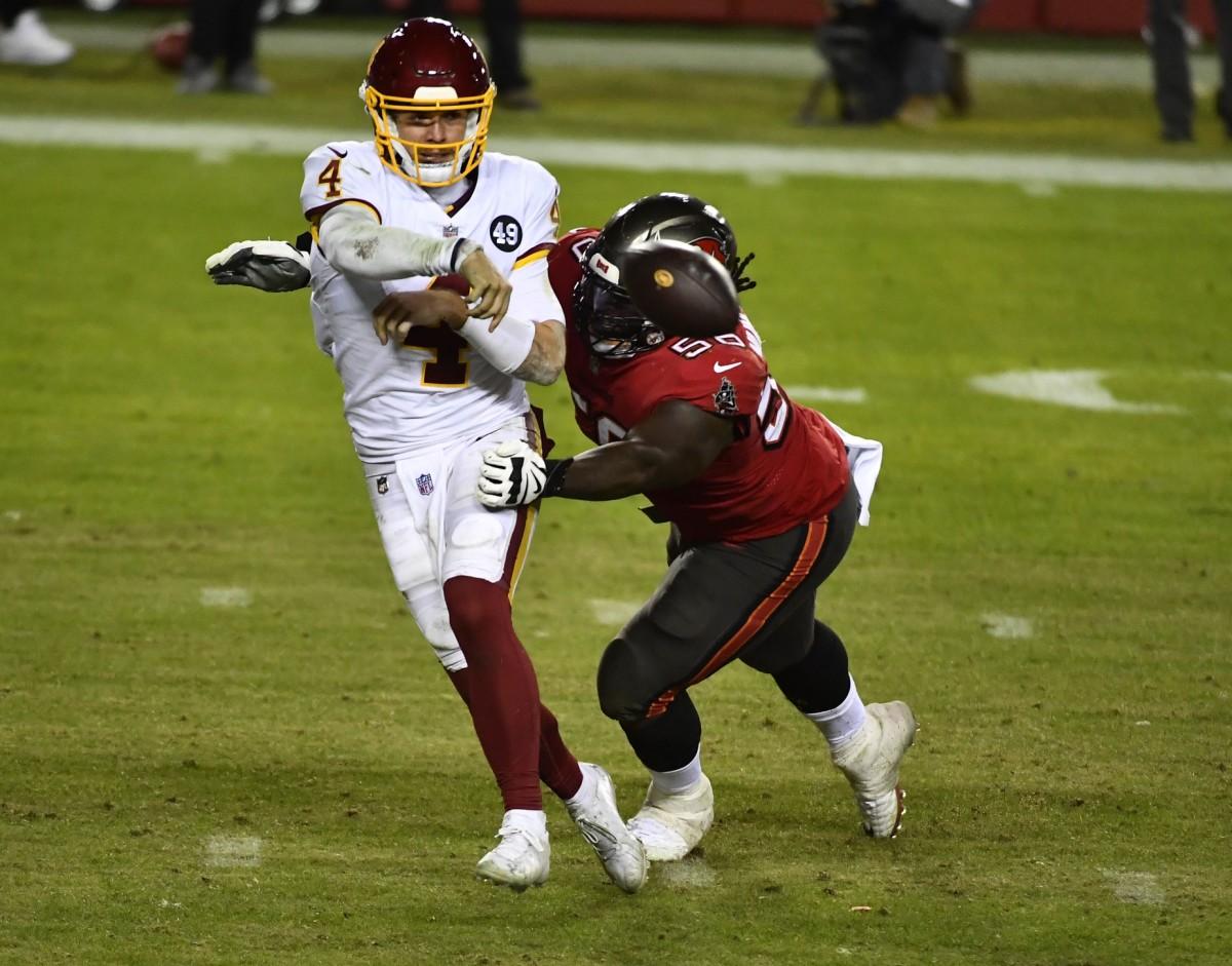 Jan 9, 2021; Landover, Maryland, USA; Washington quarterback Taylor Heinicke (4) is pressured by Tampa Bay Buccaneers defensive tackle Rakeem Nunez-Roches (56). Mandatory Credit: Brad Mills-USA TODAY
