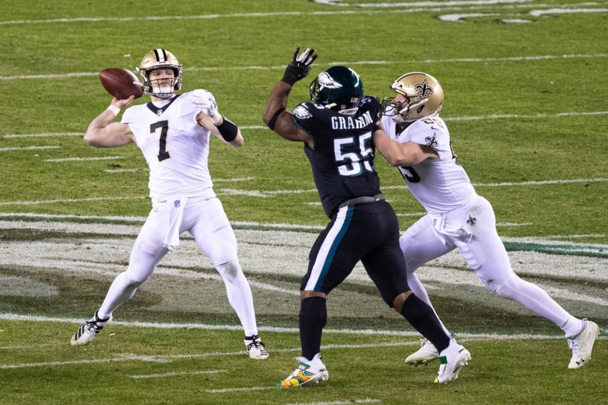 Dec 13, 2020; Philadelphia, Pennsylvania, USA; Saints quarterback Taysom Hill (7) throws a touchdown pass in front of Eagles defensive end Brandon Graham (55). Mandatory Credit: Bill Streicher-USA TODAY Sports