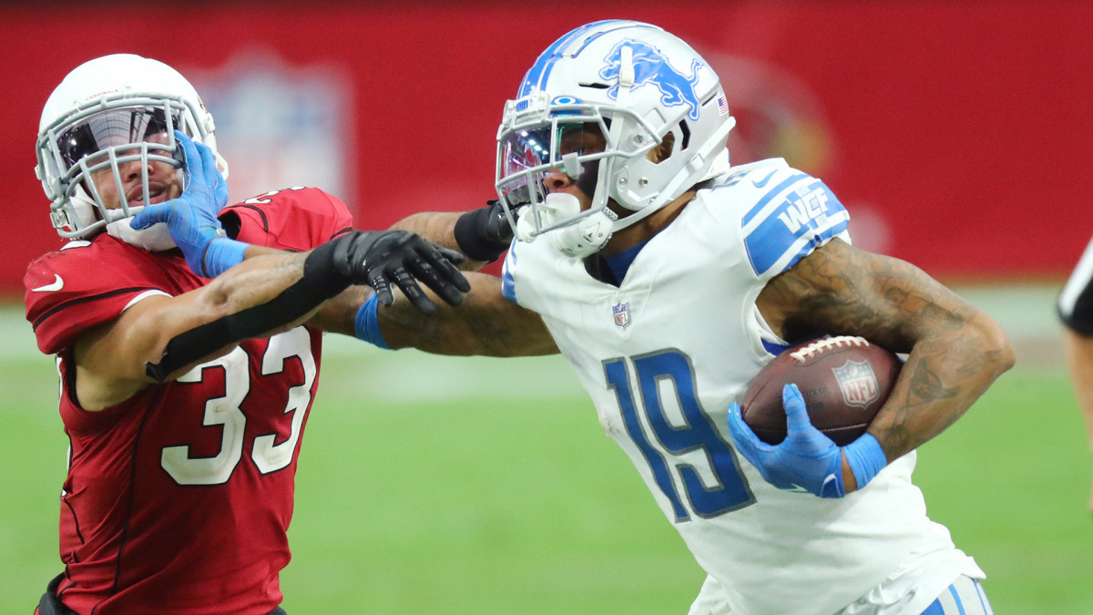Lions receiver Kenny Golladay stiff-arms a defender during a win over the Cardinals