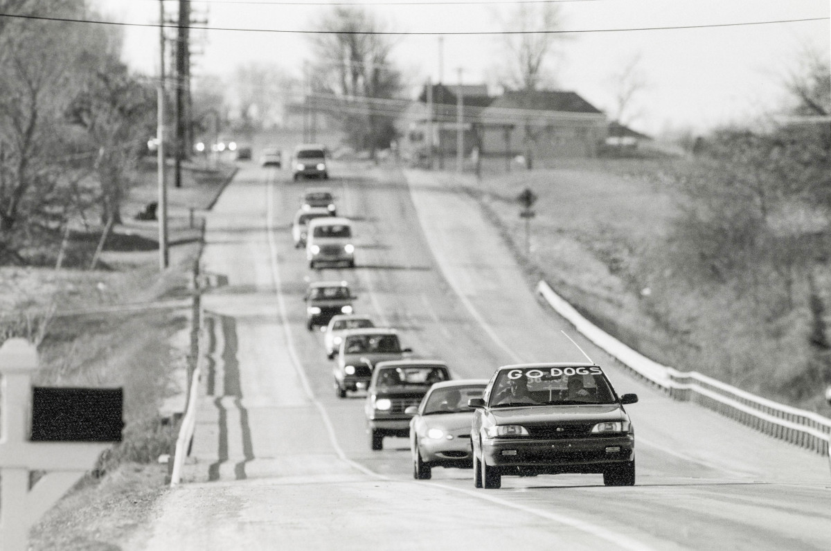 A line of cars drives to a Batesville basketball game in 1997.