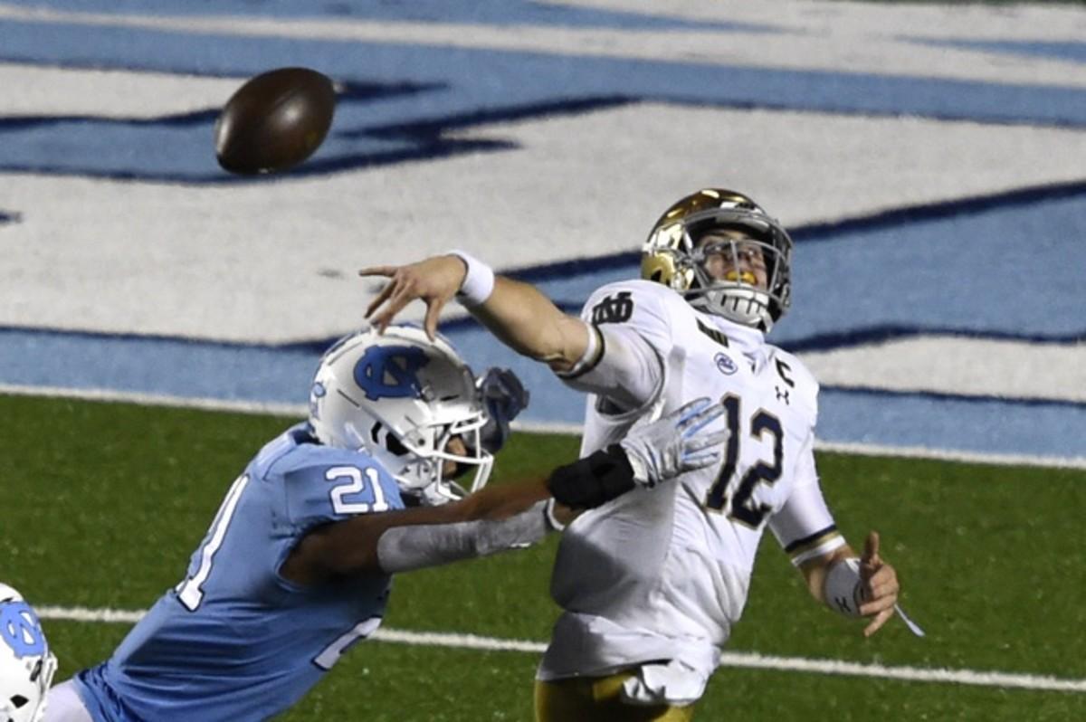 Nov 27, 2020; Chapel Hill, North Carolina, USA; Notre Dame quarterback Ian Book (12) passes the ball as North Carolina Tar Heels linebacker Chazz Surratt (21) pressures. Mandatory Credit: Bob Donnan-USA TODAY