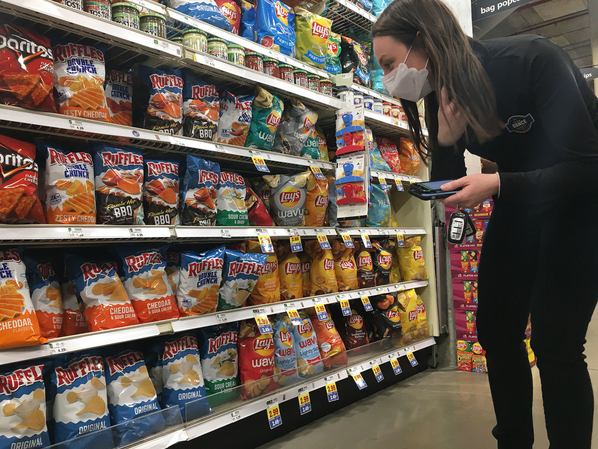 Mikela Earley searches for a bag of Ruffles original potato chips to fill an order made by a person quarantined at one of the NCAA tournament's four bubble hotels.