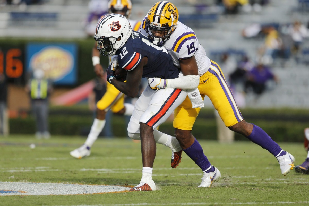 Oct 31, 2020; Auburn, Alabama, USA; Auburn receiver Eli Stove (12) is tackled by LSU linebacker Jabril Cox (21). Mandatory Credit: John Reed-USA TODAY Sports
