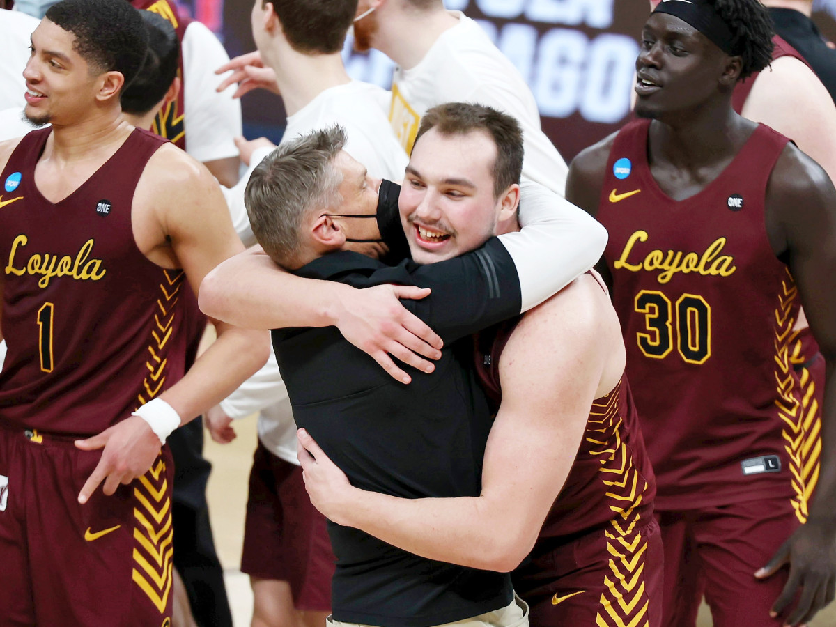 Mar 21, 2021; Indianapolis, Indiana, USA; Loyola Ramblers center Cameron Krutwig (25) hugs head coach Porter Moser after their win over the Illinois Fighting Illini in the second round of the 2021 NCAA Tournament at Bankers Life Fieldhouse. The Loyola Ramblers won 71-58.