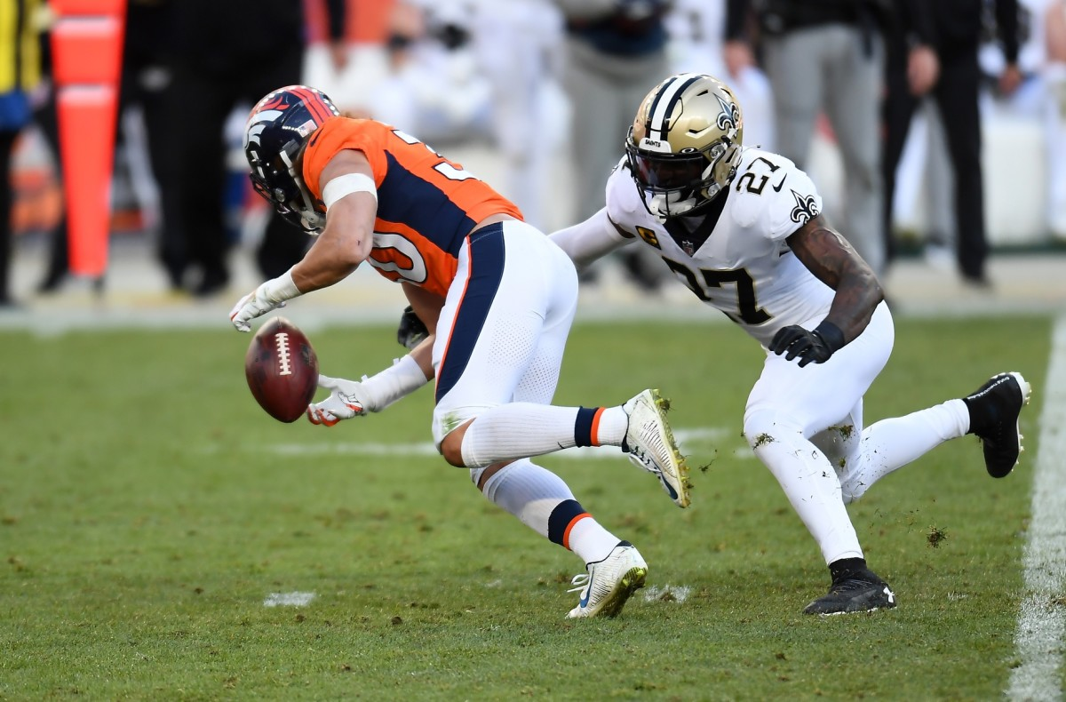 Nov 29, 2020; Denver, Colorado, USA; Broncos running back Phillip Lindsay (30) fumbles a snap against New Orleans safety Malcolm Jenkins (27). Mandatory Credit: Ron Chenoy-USA TODAY Sports