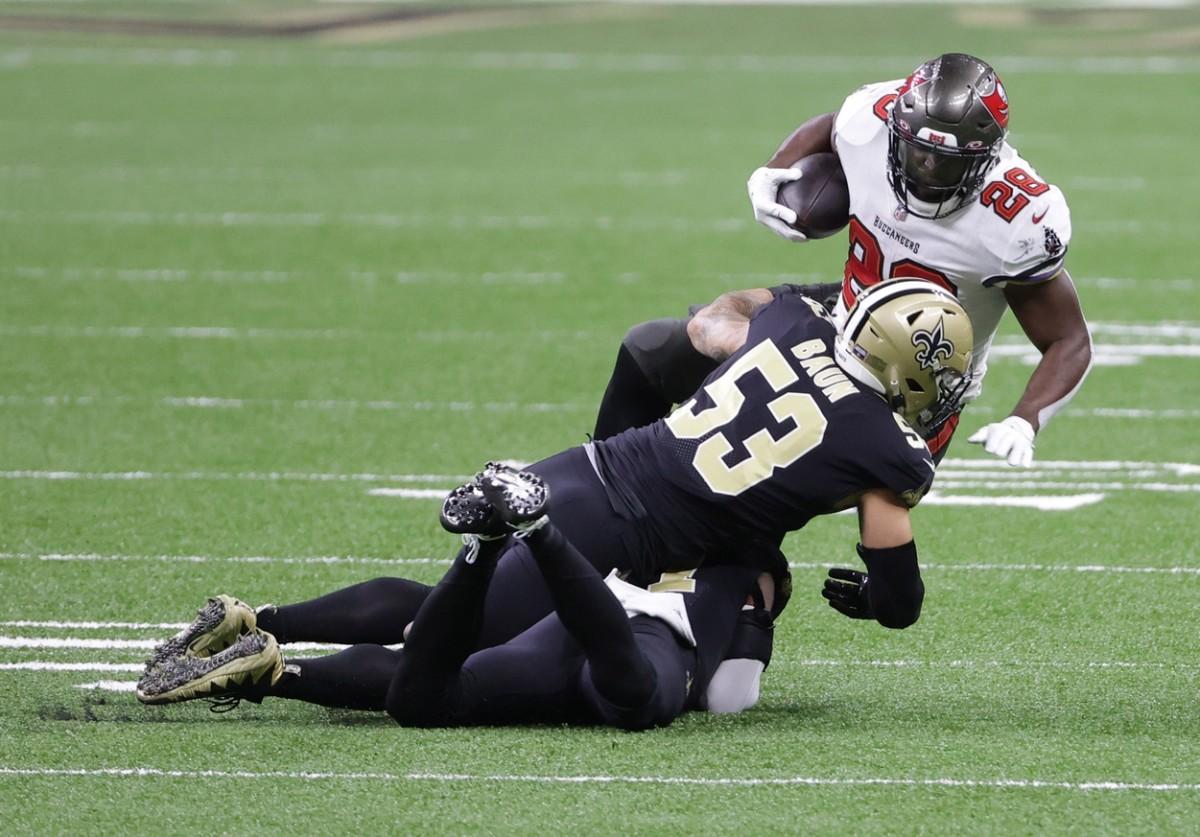 Jan 17, 2021; New Orleans, LA, USA; Tampa Bay running back Leonard Fournette (28) is tackled by Saints linebacker Zack Baun (53). Mandatory Credit: Derick E. Hingle-USA TODAY