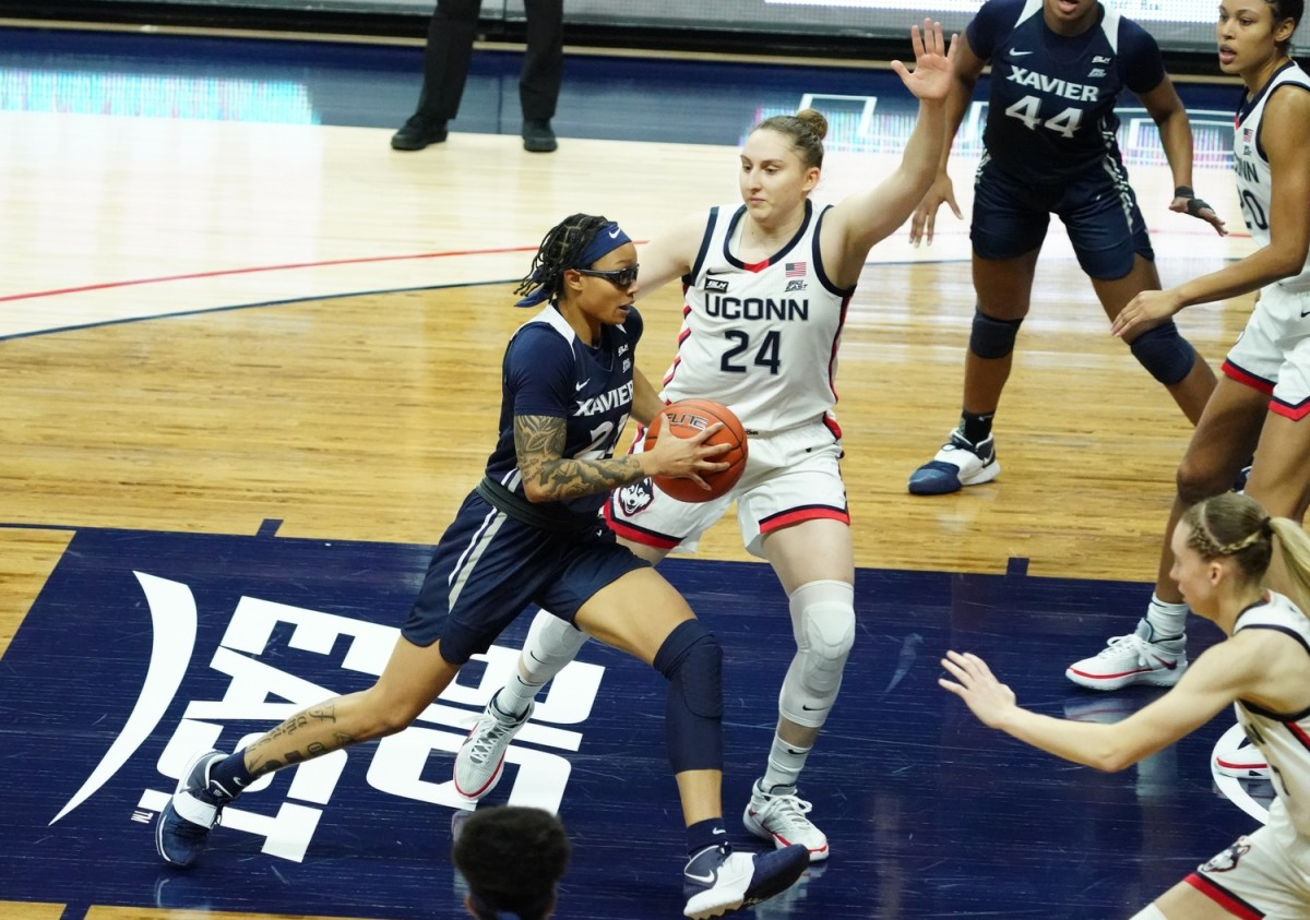 Xavier Musketeers forward A'Riana Gray (21) drives the ball against UConn Huskies guard Anna Makurat (24) in the second half at Harry A. Gampel Pavilion. UConn defeated Xavier 106-59.