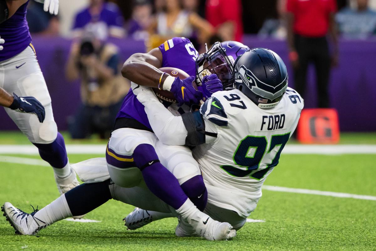 Seattle Seahawks defensive lineman Poona Ford (97) tackles Minnesota Vikings running back Alexander Mattison (25) in the first quarter at U.S. Bank Stadium.
