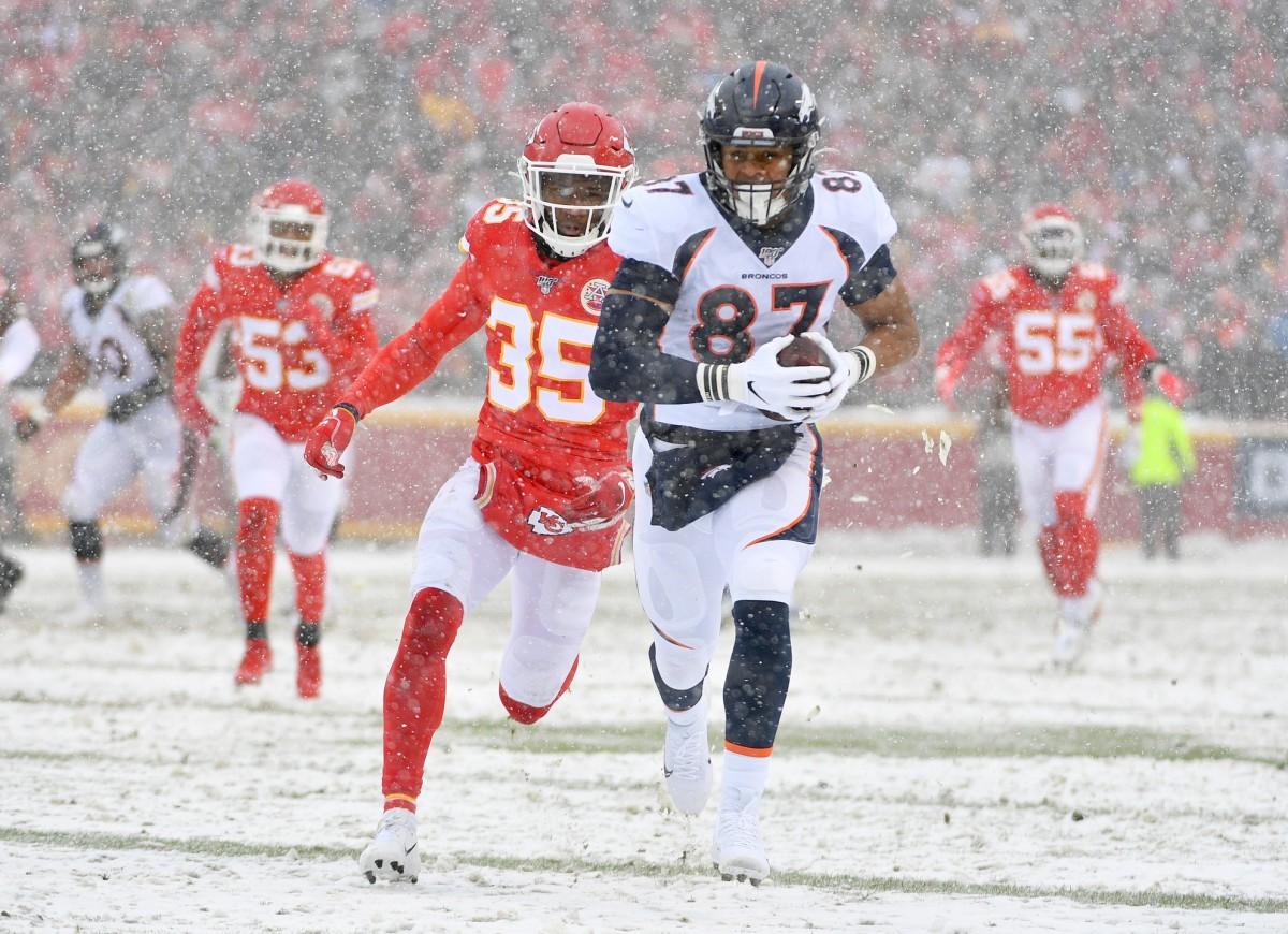 Denver Broncos tight end Noah Fant (87) runs the ball as Kansas City Chiefs cornerback Charvarius Ward (35) defends during the first half at Arrowhead Stadium.
