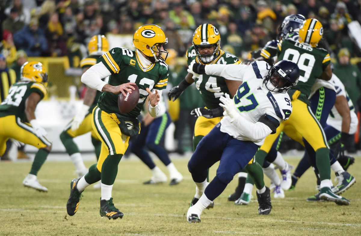 Green Bay Packers quarterback Aaron Rodgers (12) is pressured by Seattle Seahawks defensive tackle Poona Ford (97) in the first quarter of a NFC Divisional Round playoff football game at Lambeau Field.