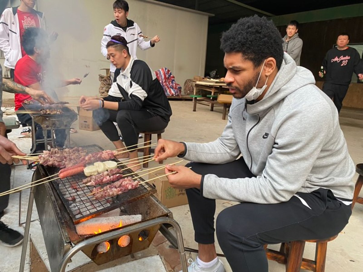 Freeman manning the grill, making connections, with Shenzhen teammates.