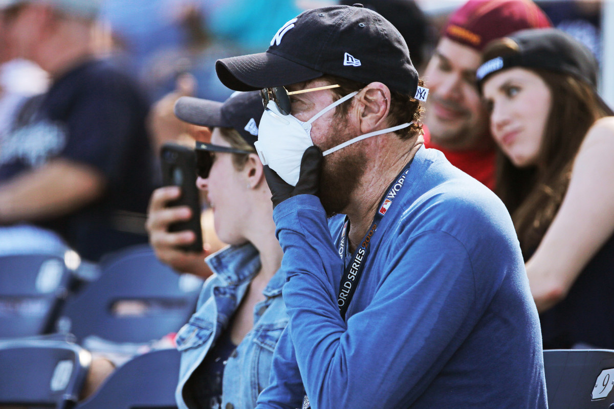 A fan wears a mask and gloves during a spring training game between the Nationals and the Yankees in Florida.