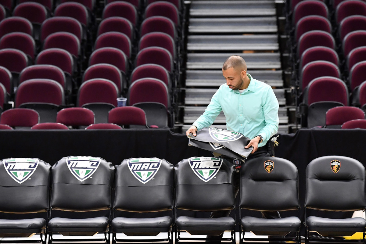 A worker removes the insignia of the Mid-American Conference from the bench chairs after the MAC tournament is cancelled.