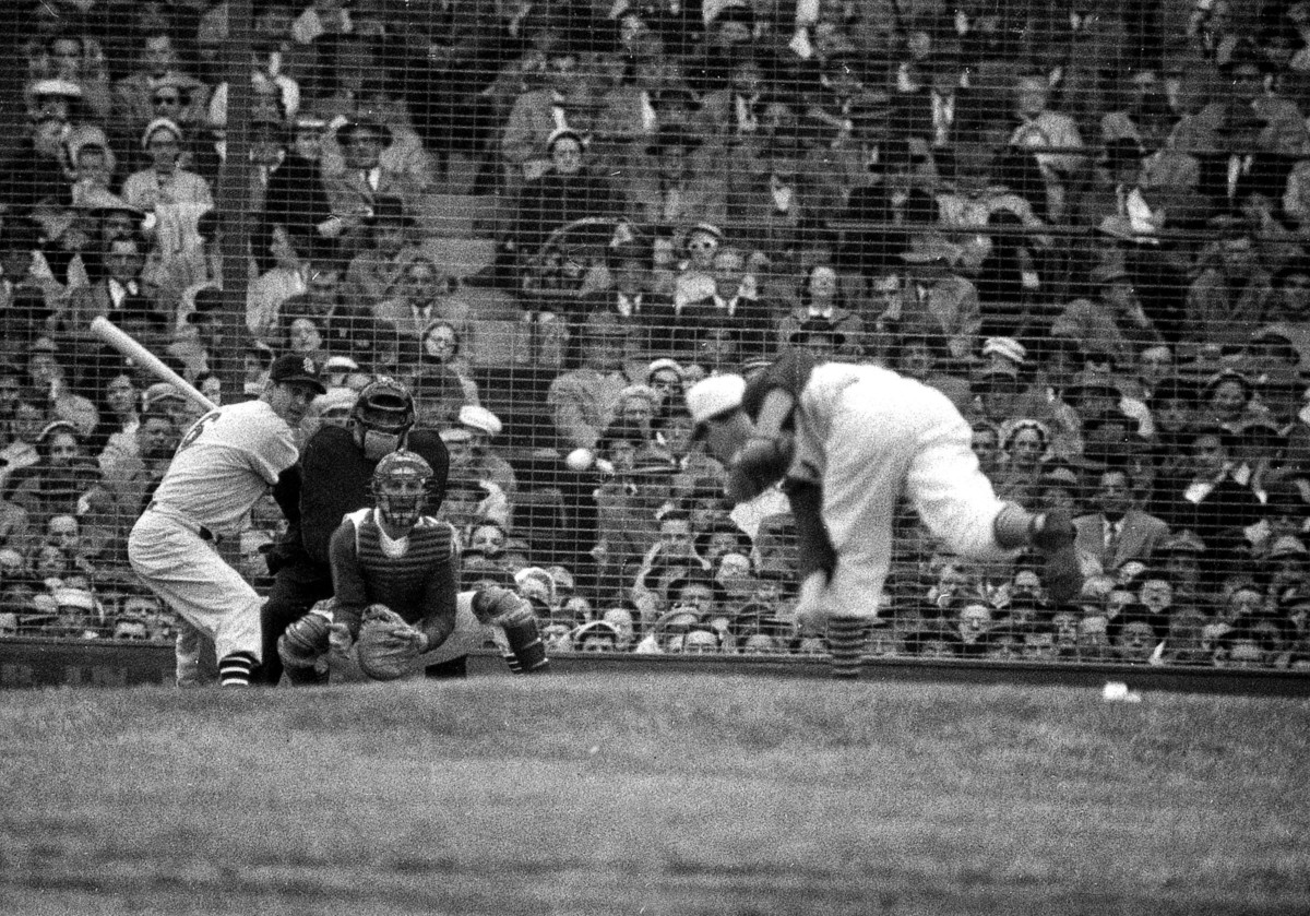 St. Louis's Stan Musial takes his licks against Cincinnati's Johnny Klippstein at Crosley Field on Opening Day in 1957.