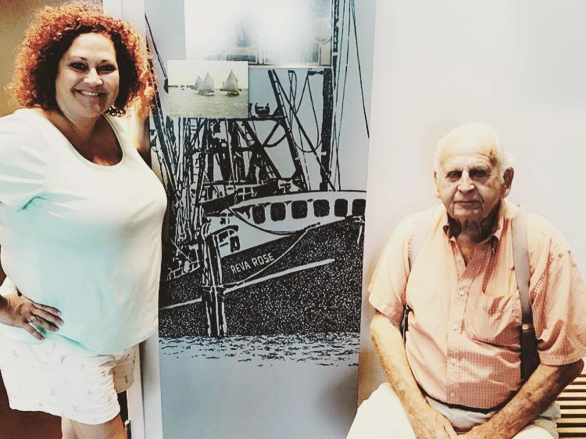 Tommy Schultz and his daughter, Reva Hopkins, pose next to a photo of Captain Tommy's shrimp boat, the Reva Rose.