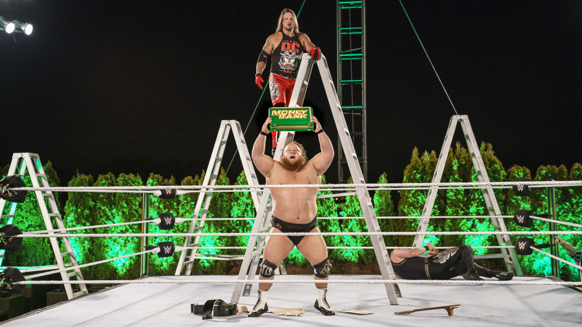 WWE's Otis holds the Money in the Bank briefcase after winning the ladder match