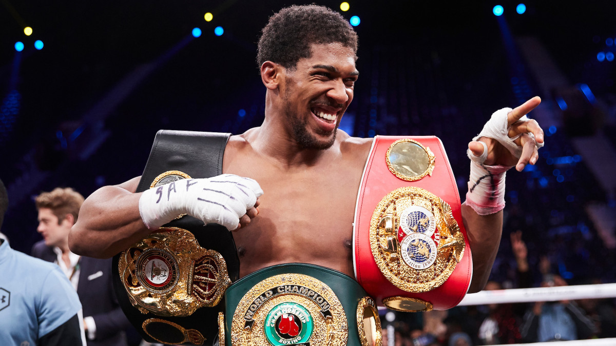Boxer Anthony Joshua poses with his heavyweight championship belts after defeating Andy Ruiz in Saudi Arabia.