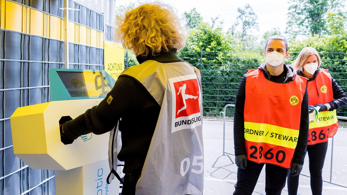 Stadium stewards sanitize their hands before Dortmund vs. Schalke