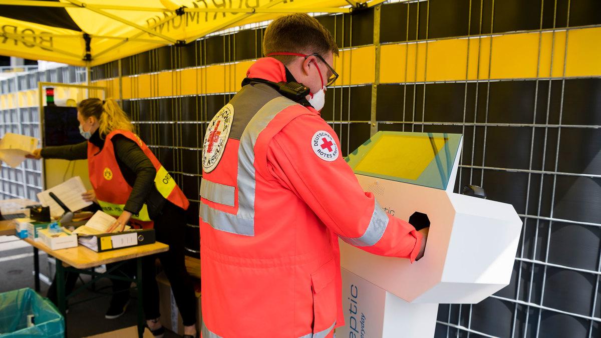 A medical staffer sanitizes his hands before Dortmund vs. Schalke
