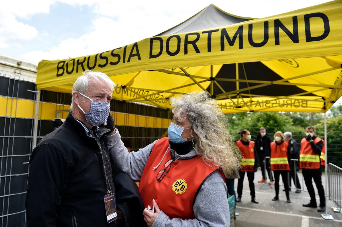A member of the TV broadcast crew gets his temperature taken at Dortmund's stadium.