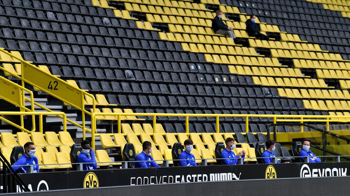 Schalke substitutes sit spread apart in the Dortmund stands