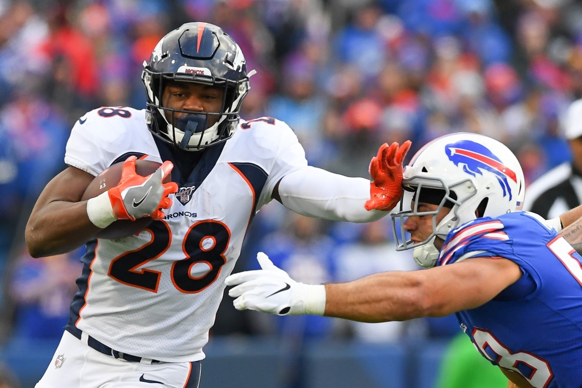 Denver Broncos running back Royce Freeman (28) runs with the ball as Buffalo Bills outside linebacker Matt Milano (58) defends during the third quarter at New Era Field.
