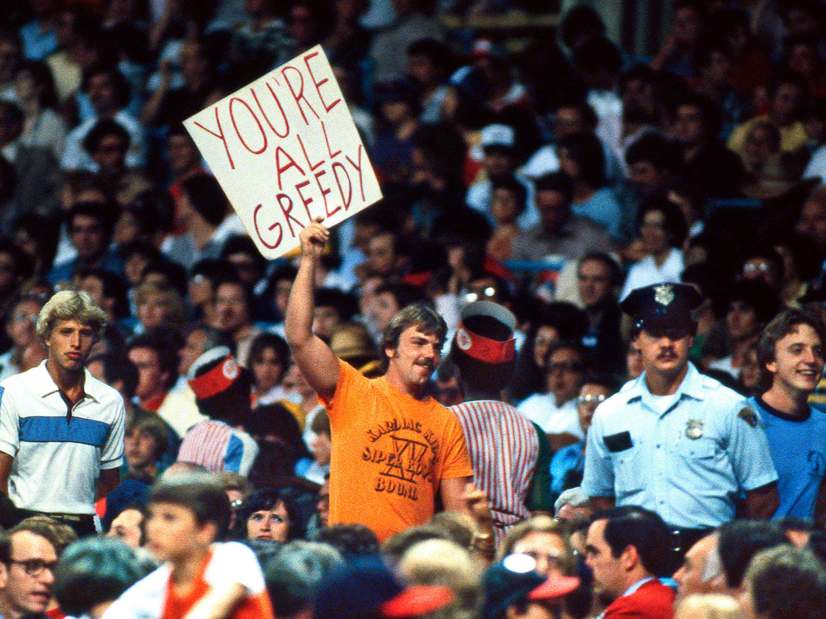"Baseball fan holds up a sign attacking players and owners: ""YOU'RE ALL GREEDY"""