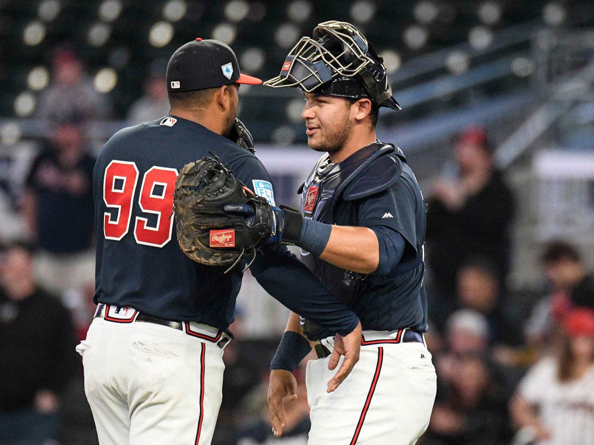 Catcher Alex Jackson puts his arm around another Braves pitcher.