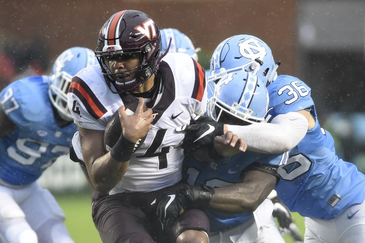 Oct 8, 2016; Chapel Hill, NC, USA; Virginia Tech Hokies quarterback Jerod Evans (4) is tackled by North Carolina Tar Heels linebackers Andre Smith (10) and Cole Holcomb (36) in the first half at Kenan Memorial Stadium. Mandatory Credit: Bob Donnan-USA TODAY Sports