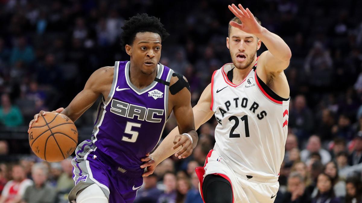 De'Aaron Fox dribbles the ball past Toronto Raptors guard Matt Thomas