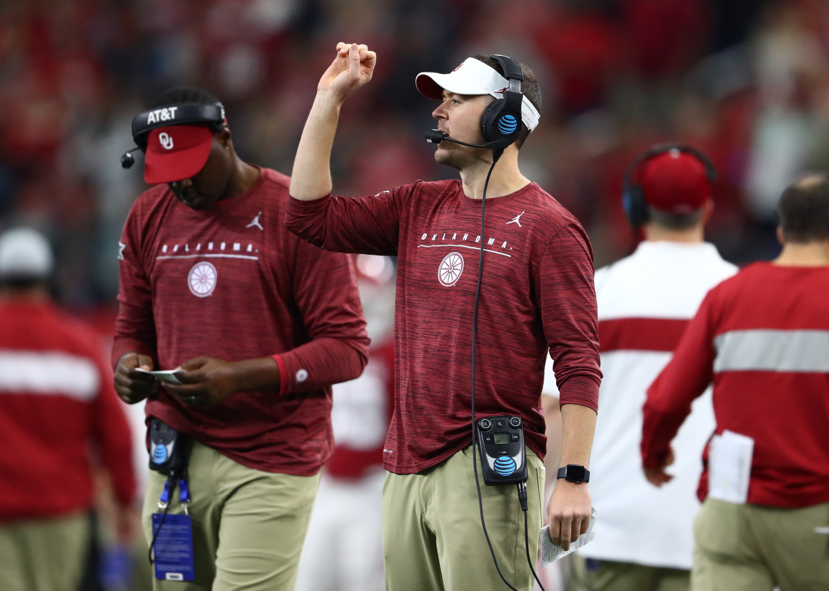 Lincoln Riley signals in from his play sheet.