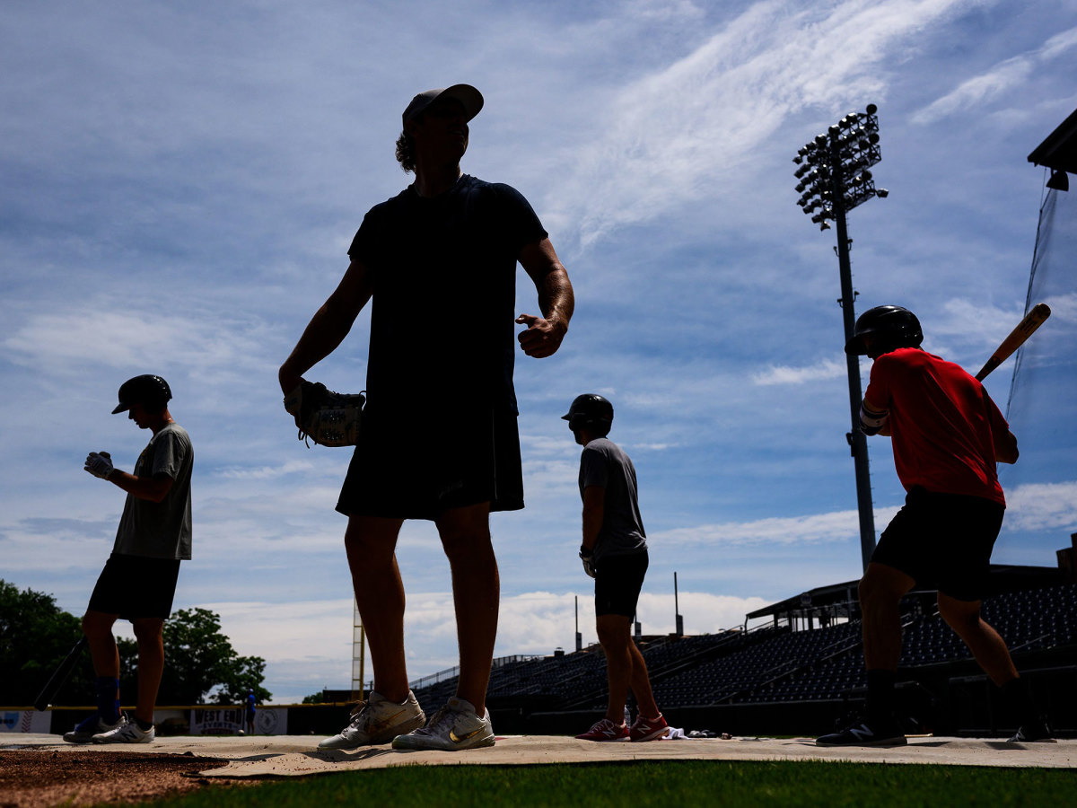 Minor league baseball players stand on a field.