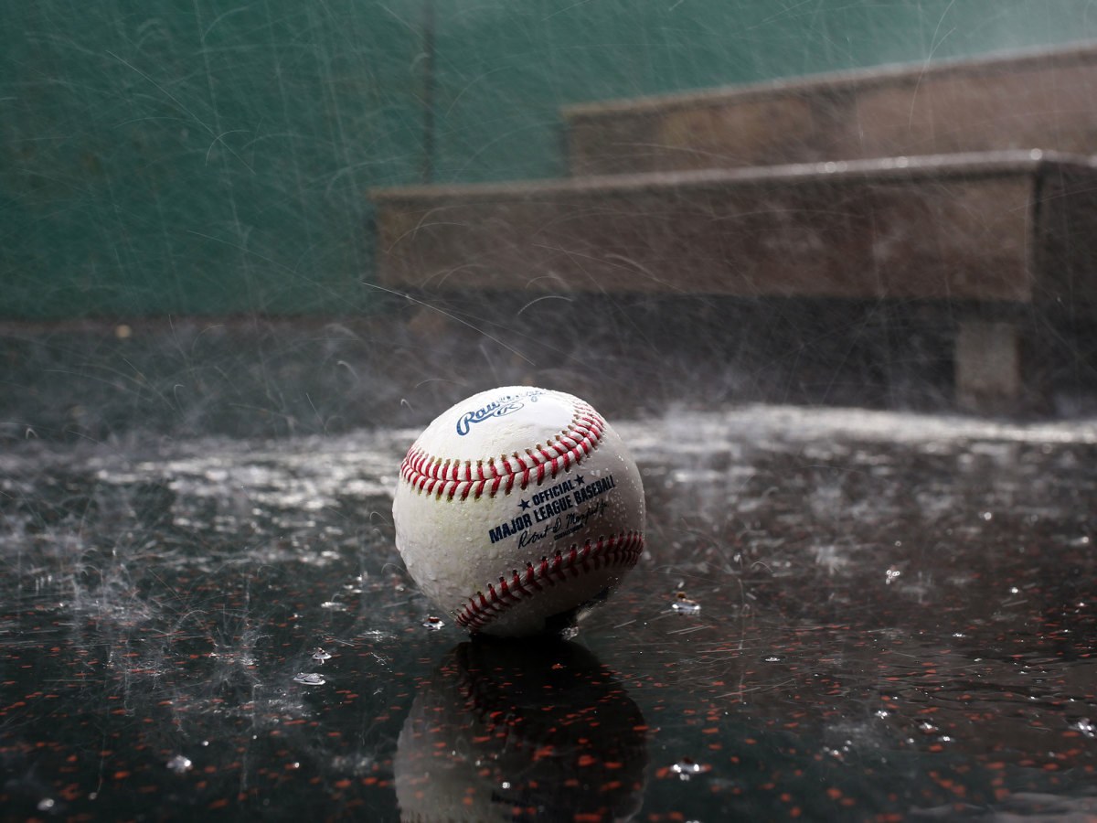 A baseball left on the ground in the rain