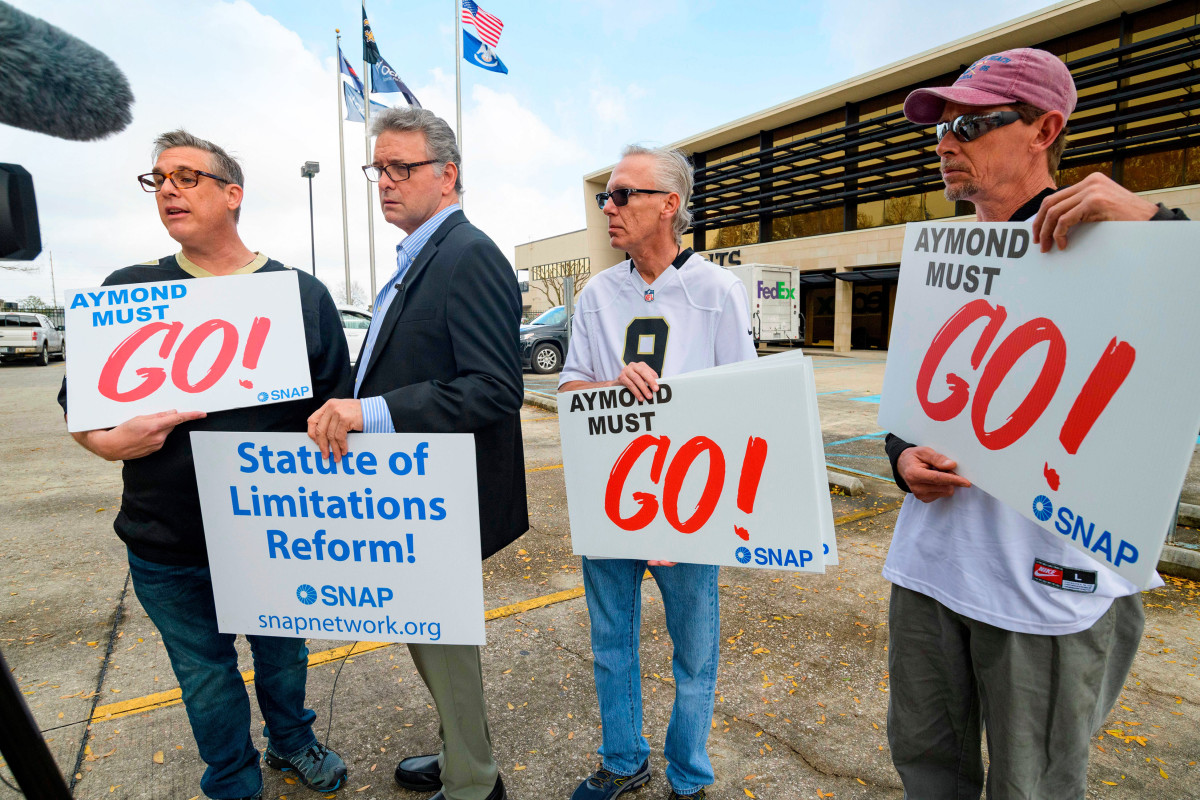 Four men holding signs reading Aymond must go