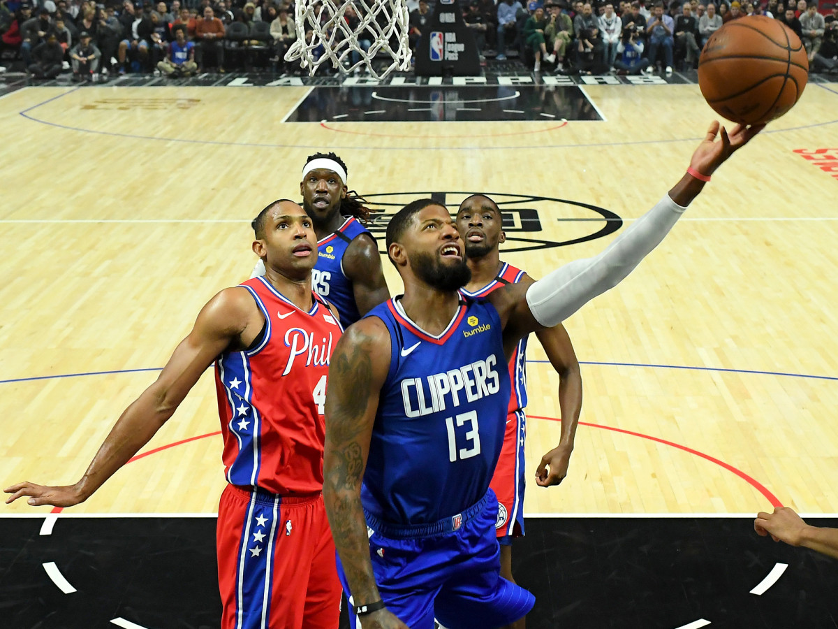 March 1, 2020; Los Angeles, California, USA; Los Angeles Clippers security guard Paul George (13) comes from Al Horford (42), striker of the Philadelphia 76ers, as he drives to the basket in the first half of the game at Staples Center.