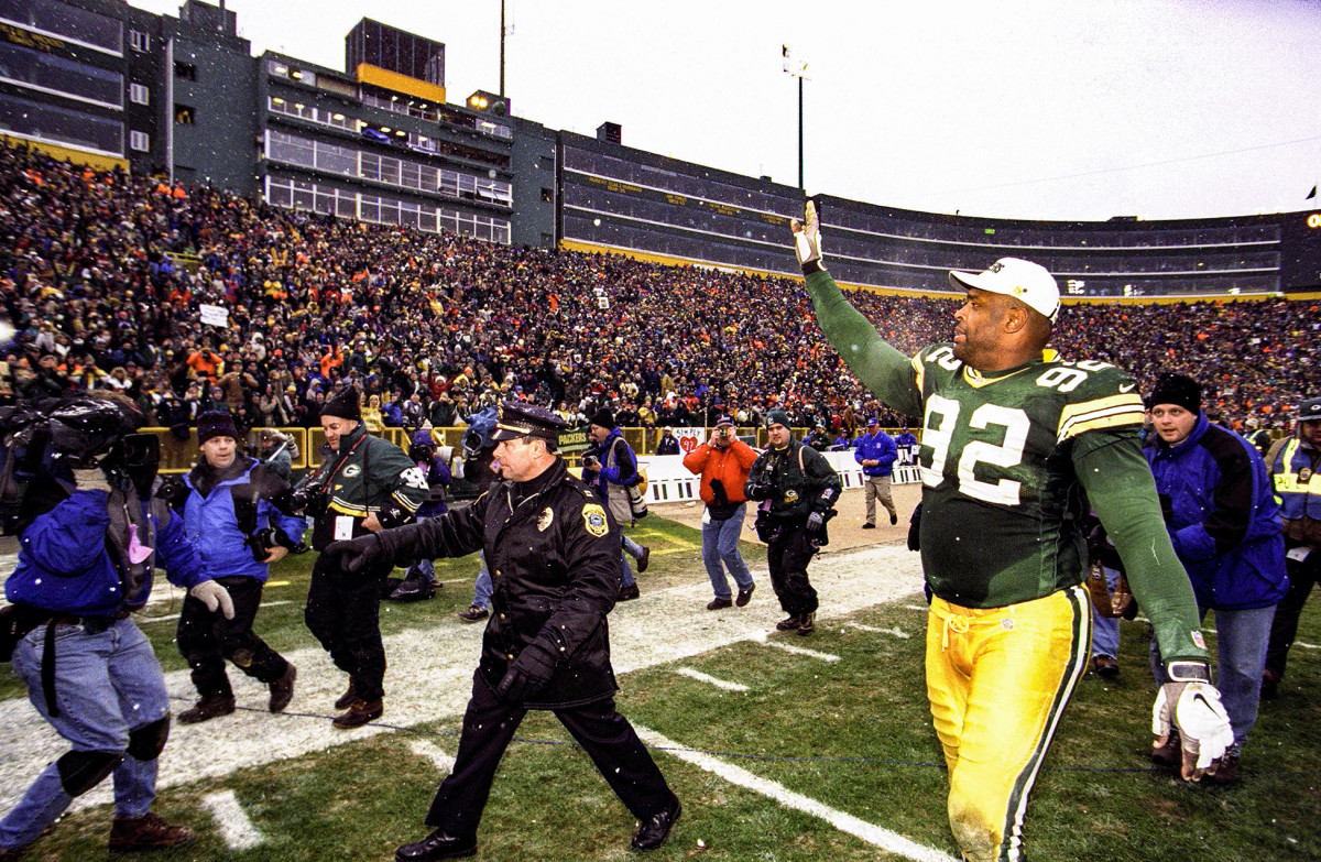 Packers legend Reggie White waves to the crowd as he leaves Lambeau Field