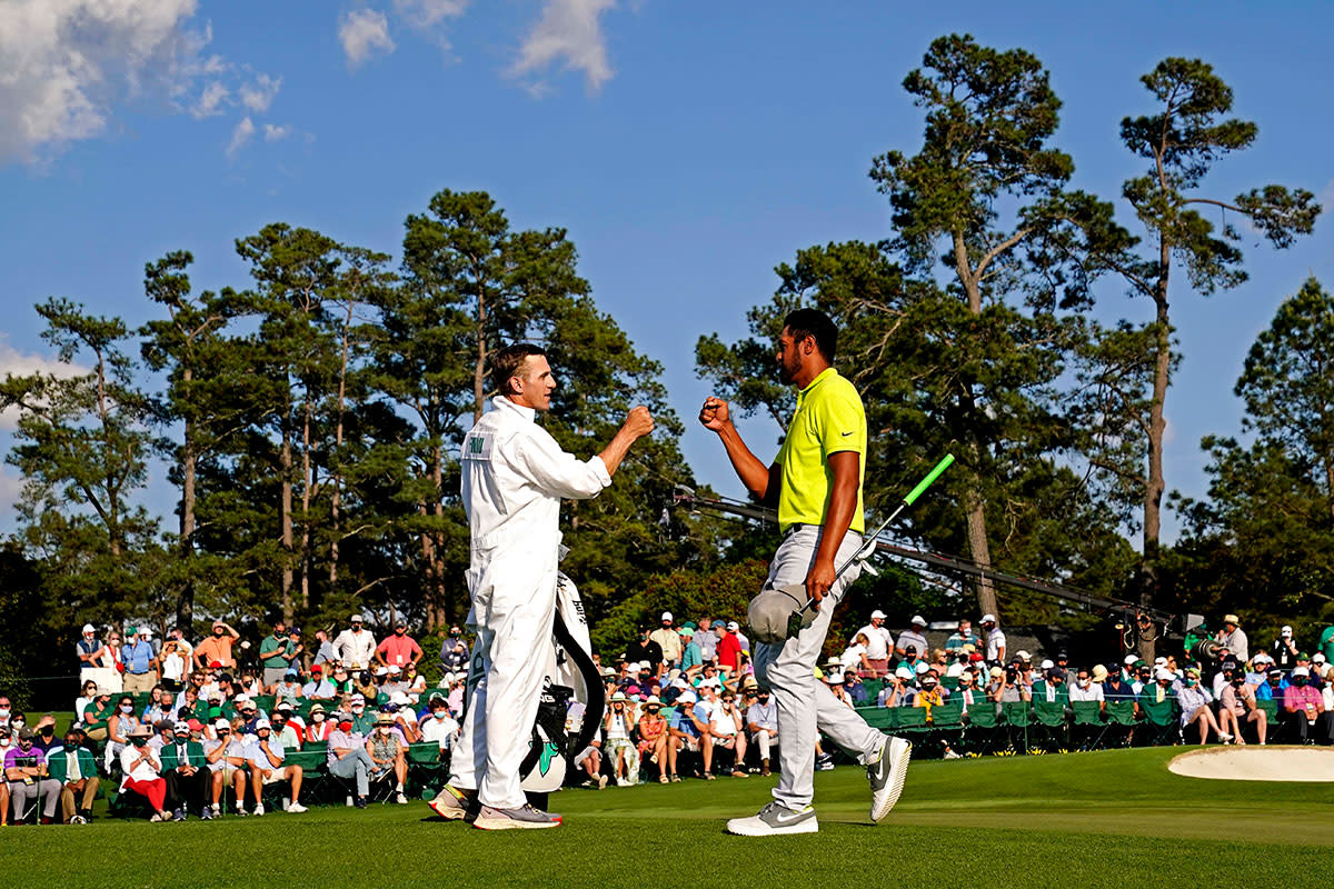 Mark Urbanek and Tony Finau fist-bump on the 18th green during the final round of the Masters.