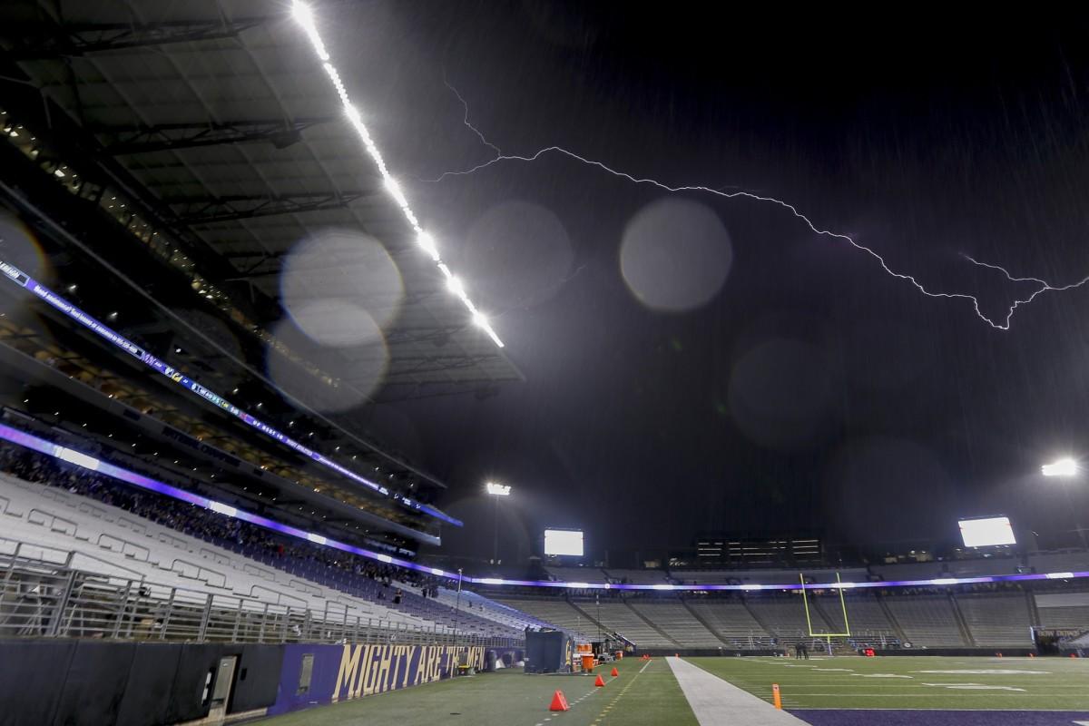 A lightning bolt streaks over Husky Stadium in 2019.