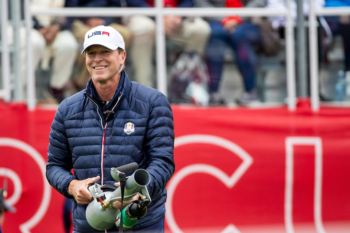 """Steve Stricker holds a T-shirt """"cannon"""" at the 2021 Ryder Cup."""