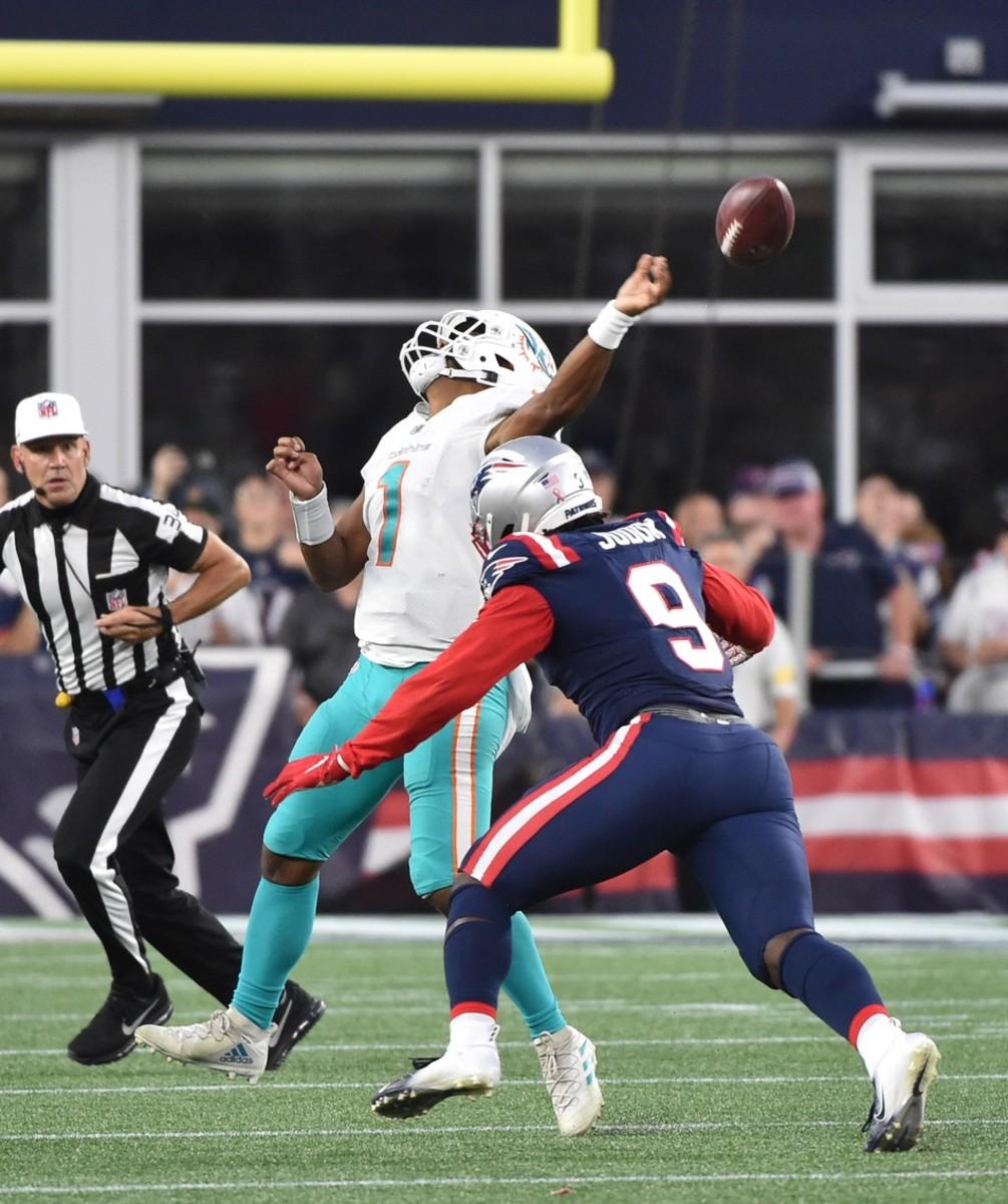 Miami Dolphins quarterback Tua Tagovailoa (1) throws the ball prior to getting hit by New England Patriots linebacker Matt Judon (9). Mandatory Credit: Bob DeChiara-USA TODAY Sports